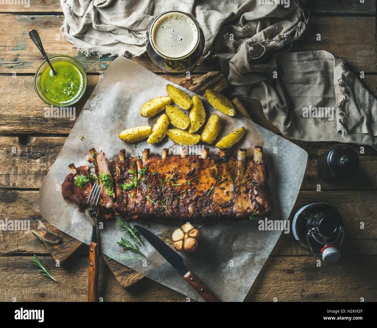 Arrosto di maiale nervature parzialmente tagliato a pezzi con aglio, rosmarino, salsa alle erbe verdi, patate fritte Immagini Stock