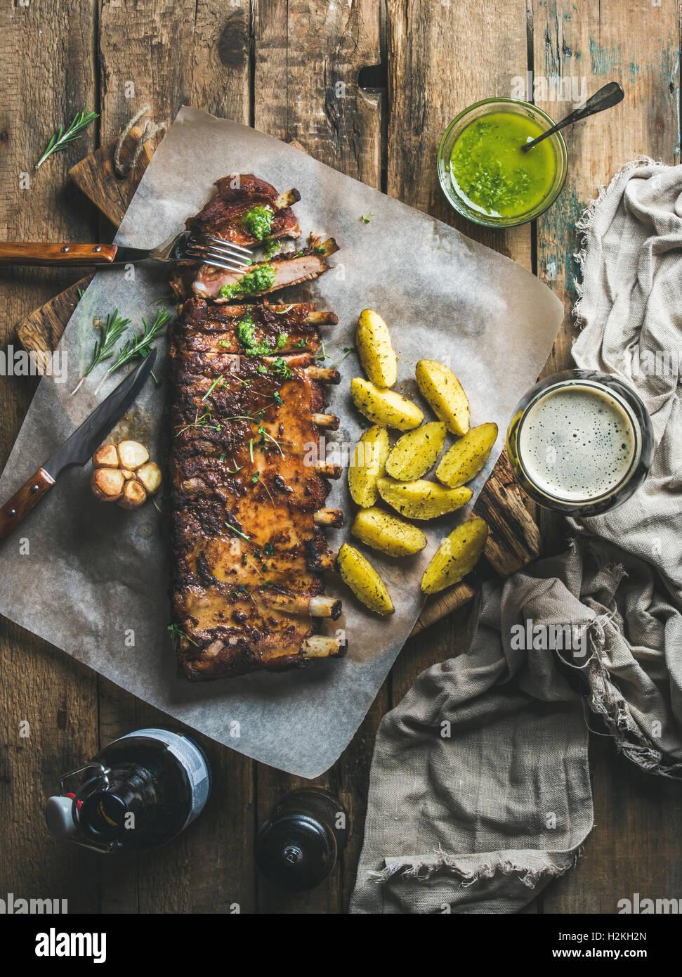 Arrosto di costolette di maiale con aglio, rosmarino, salsa alle erbe verdi, patate fritte e birra scura sul legno Immagini Stock