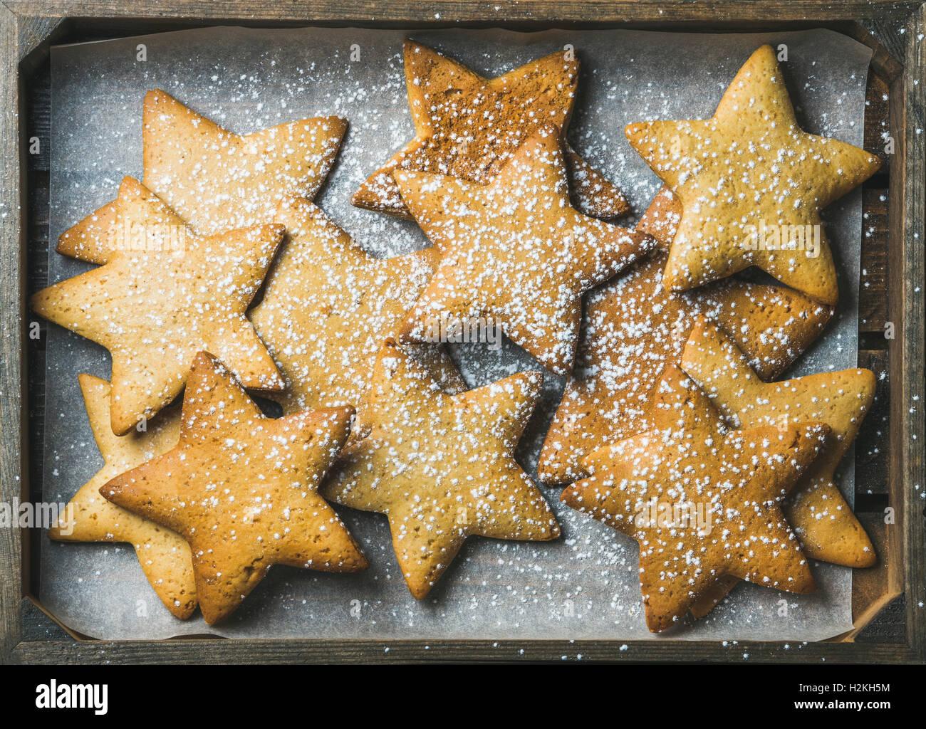 Dolce Natale gingerbread cookies in forma di stelle con lo zucchero in polvere sulla carta da forno in legno rustico Immagini Stock