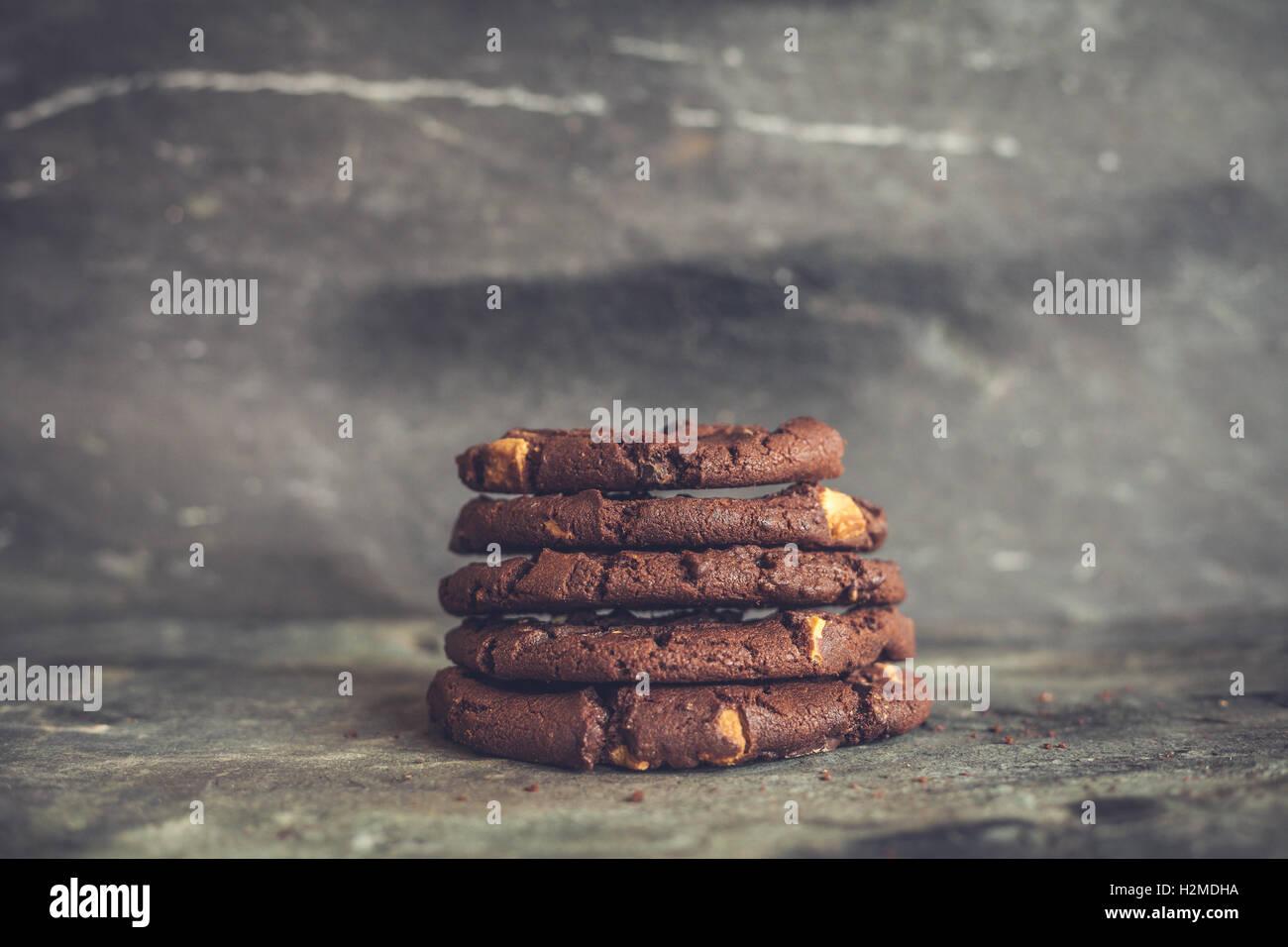 Biscotti al cioccolato impilati su un sfondo di ardesia Immagini Stock