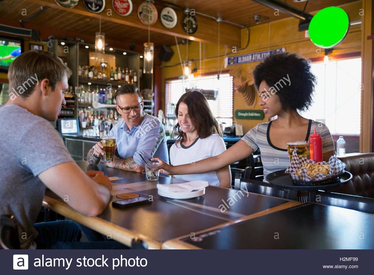 La cameriera che serve cibo e bevande per gli amici a tavola in bar Immagini Stock