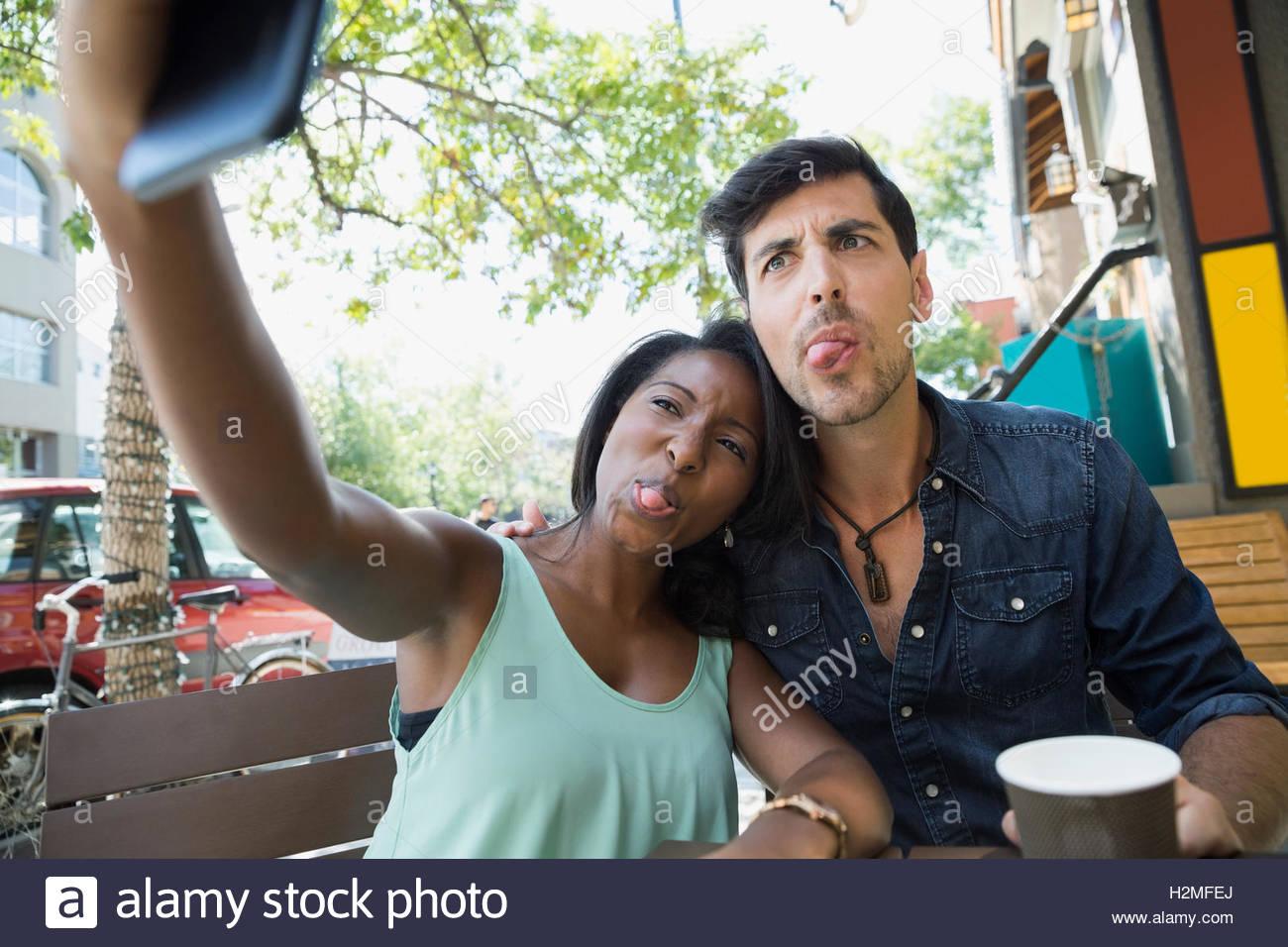 Giocoso giovane rendendo silly volti e tenendo selfie con la fotocamera del telefono al cafè sul marciapiede Immagini Stock
