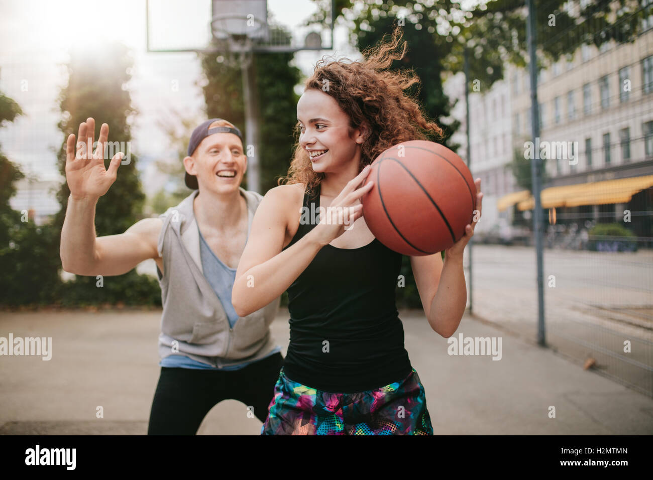 Ragazza giovane giocare a basket con ragazzo bloccando. Amici di adolescenti godendo di un gioco di streetball sulla Immagini Stock