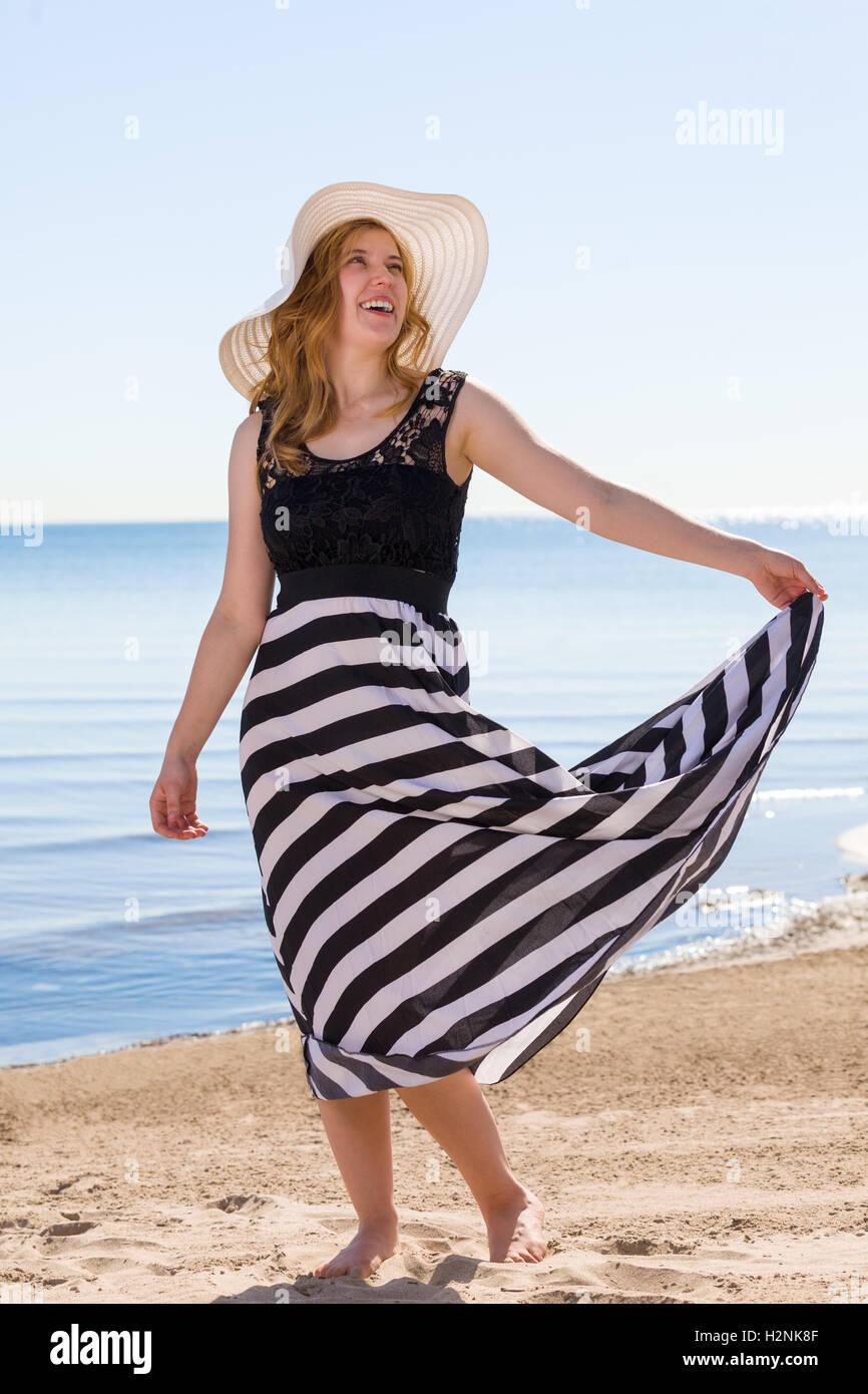 Bella donna in un bianco e nero sun-dress camminando lungo la spiaggia. Immagini Stock