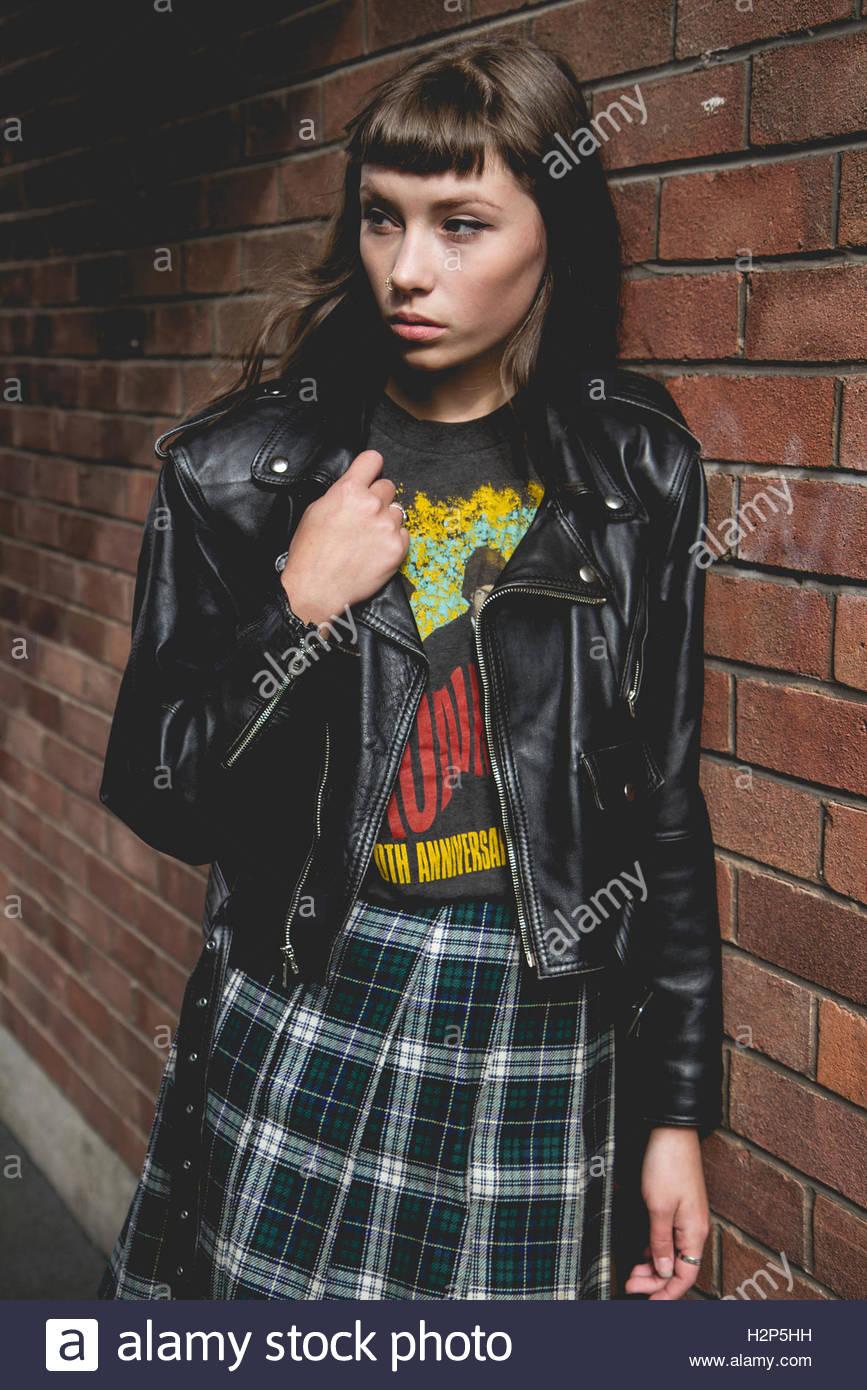 Bruna modello con una frangia indossa band tee e cuoio nero biker giacca e  gonna tartan 1c9cd51f75c8