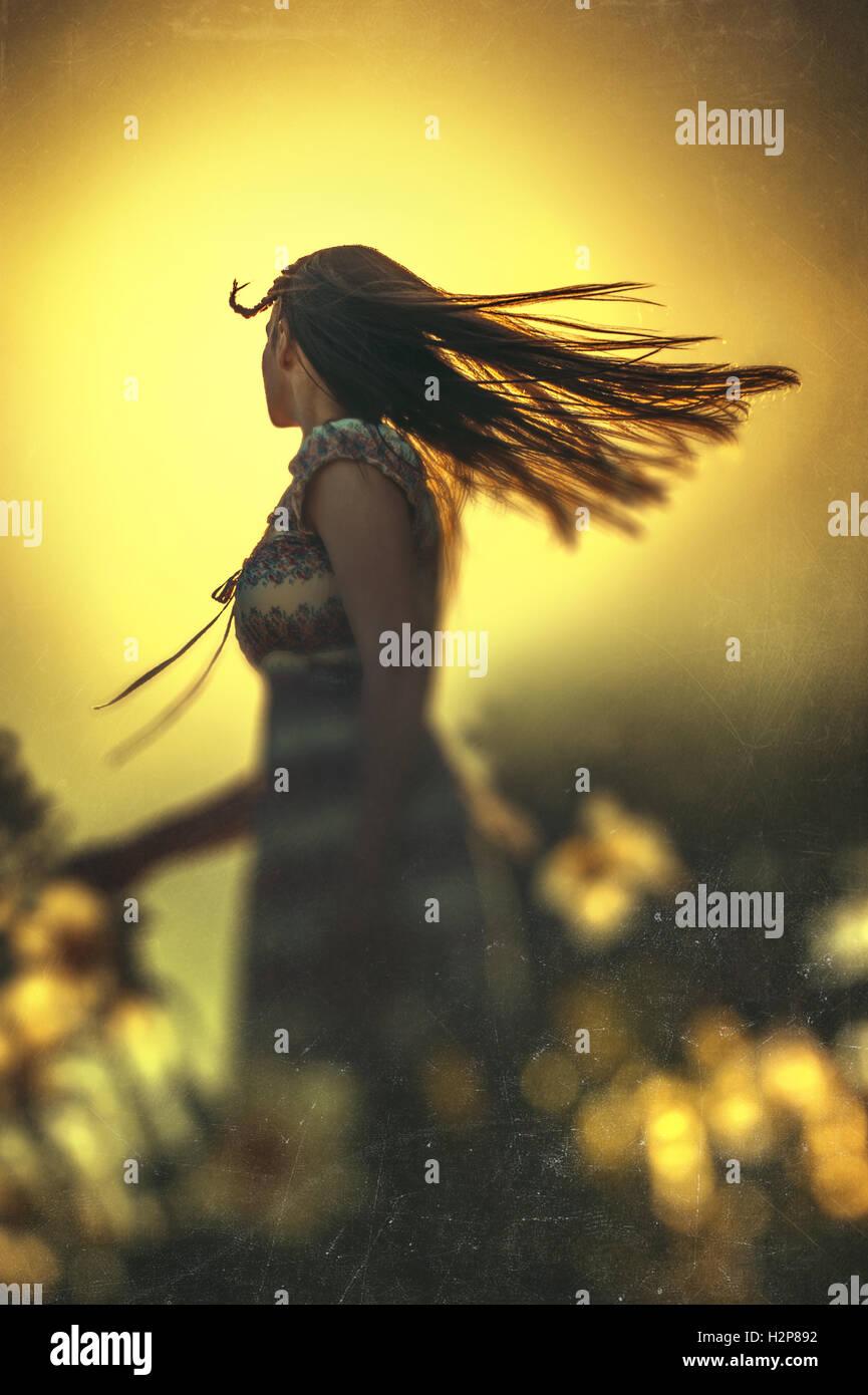 Felice giovane donna dancing in prato estivo con fiori di colore giallo Immagini Stock