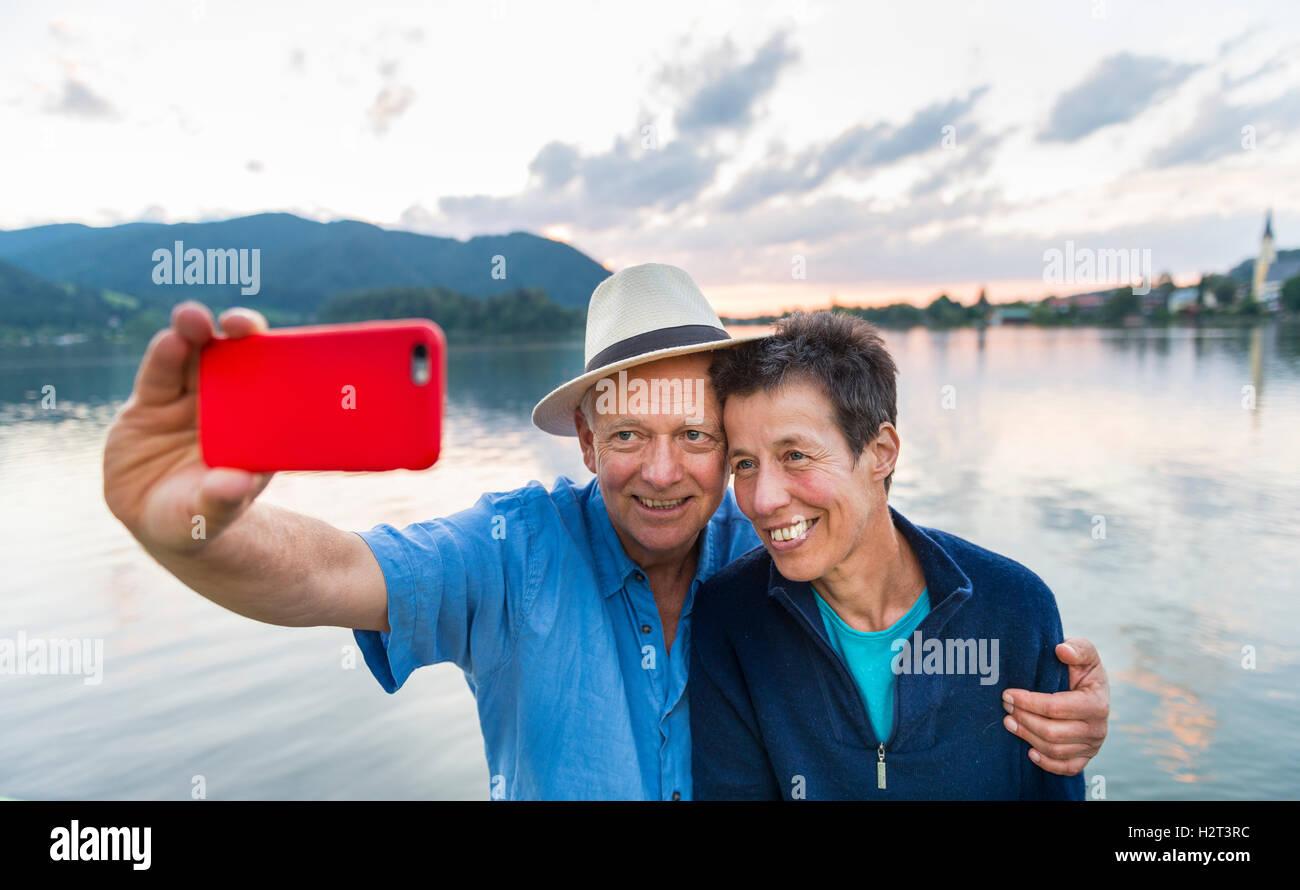 Uomo e donna sorridente, prendendo foto con il telefono cellulare, selfie, Schliersee, Alta Baviera, Baviera, Germania Immagini Stock