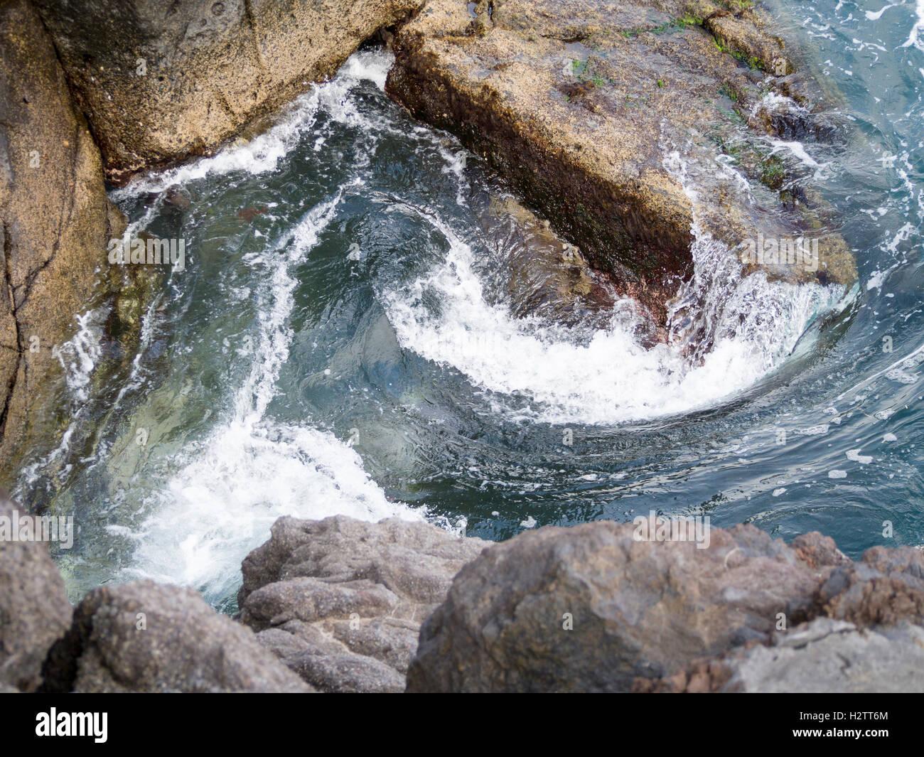 Surf vorticoso intorno alle rocce. L'acqua dalle onde colpire la costa rocciosa e curl in una vasca idromassaggio Immagini Stock