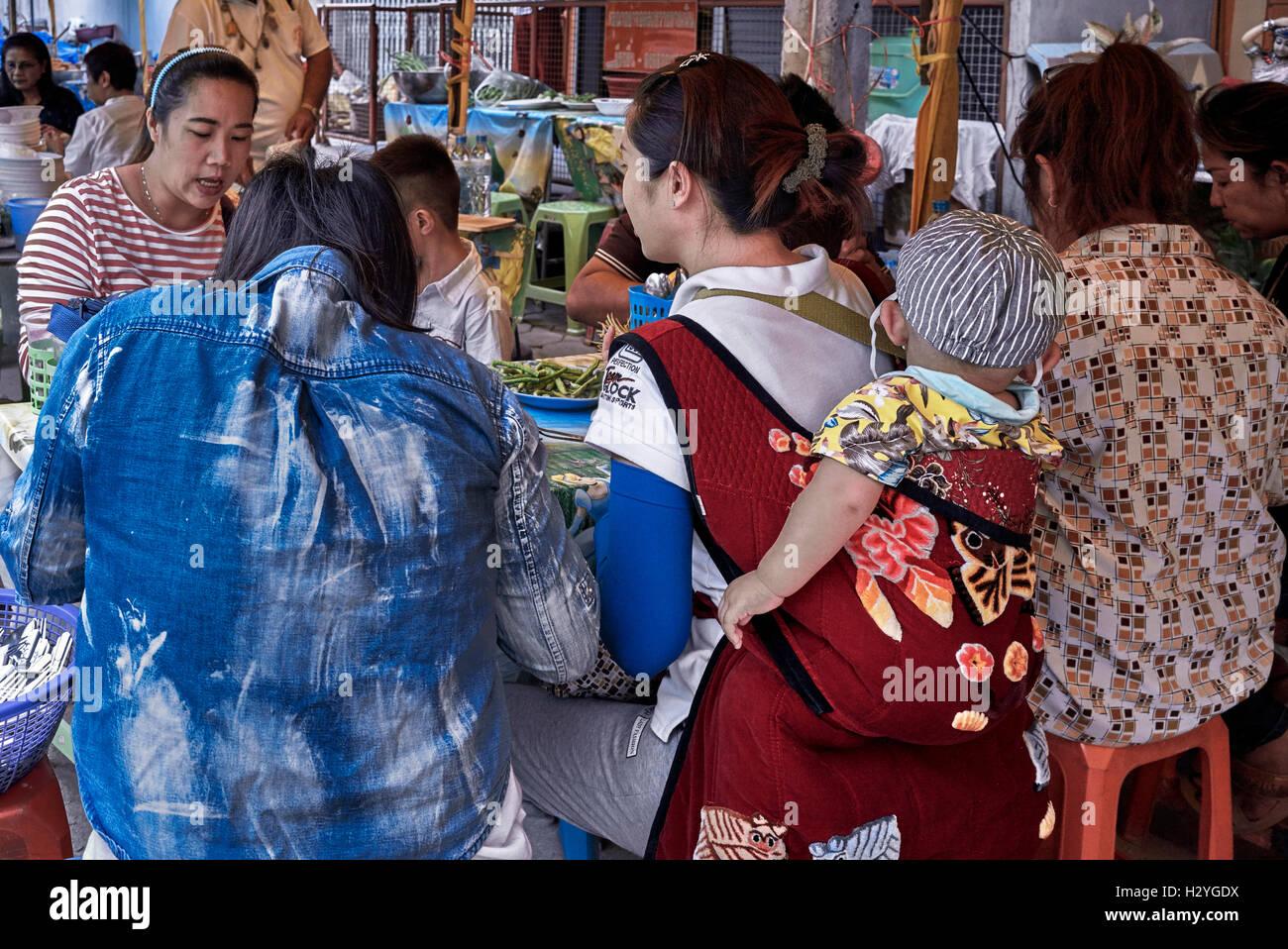 Thai la madre e il bambino portato in una imbragatura posteriore cablaggio e mangiare in un ristorante a cielo aperto. Immagini Stock