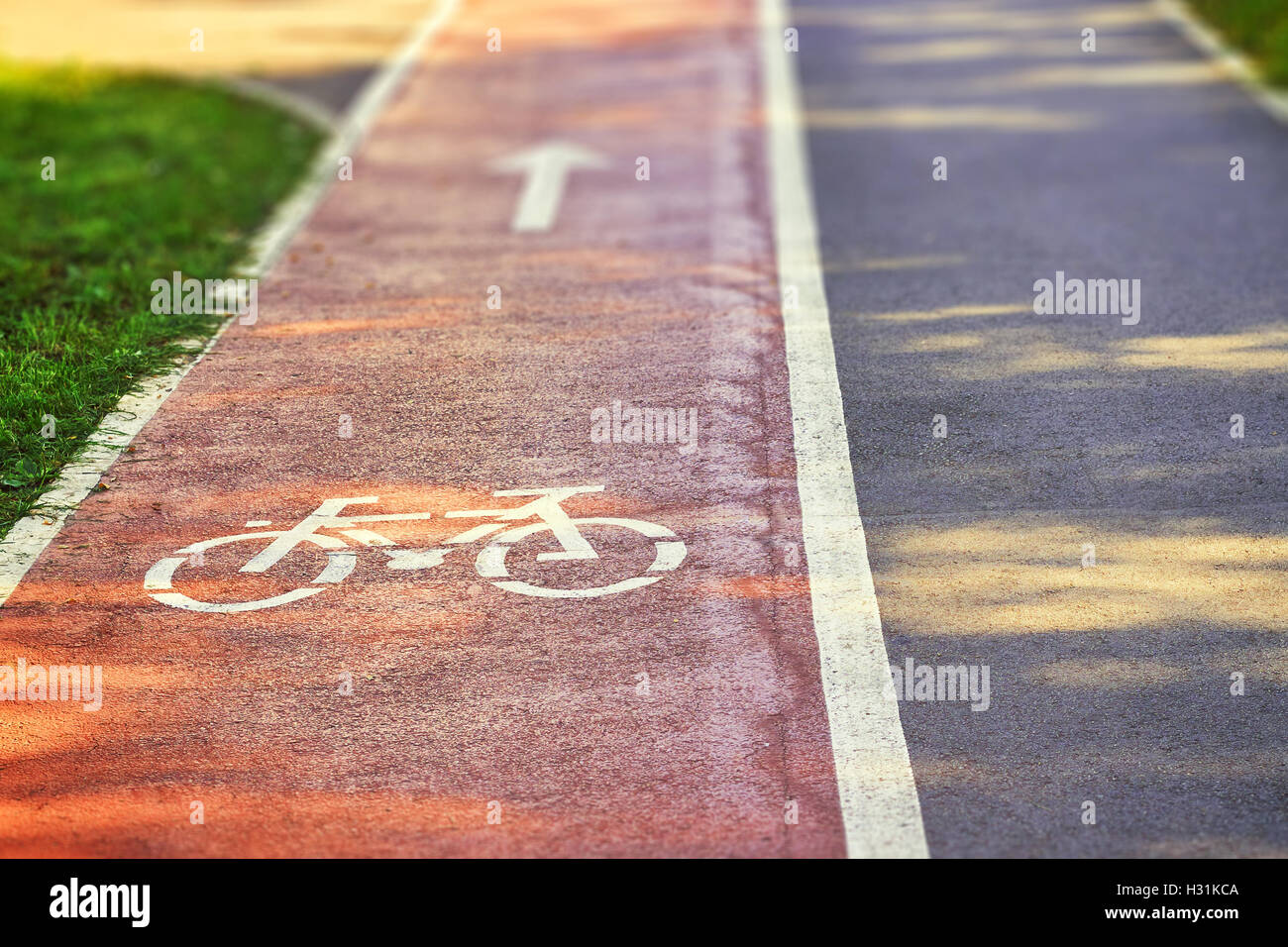 Rosso pista ciclabile sul marciapiede con dipinto di bianco in bicicletta e freccia segni. Spazio di copia Immagini Stock