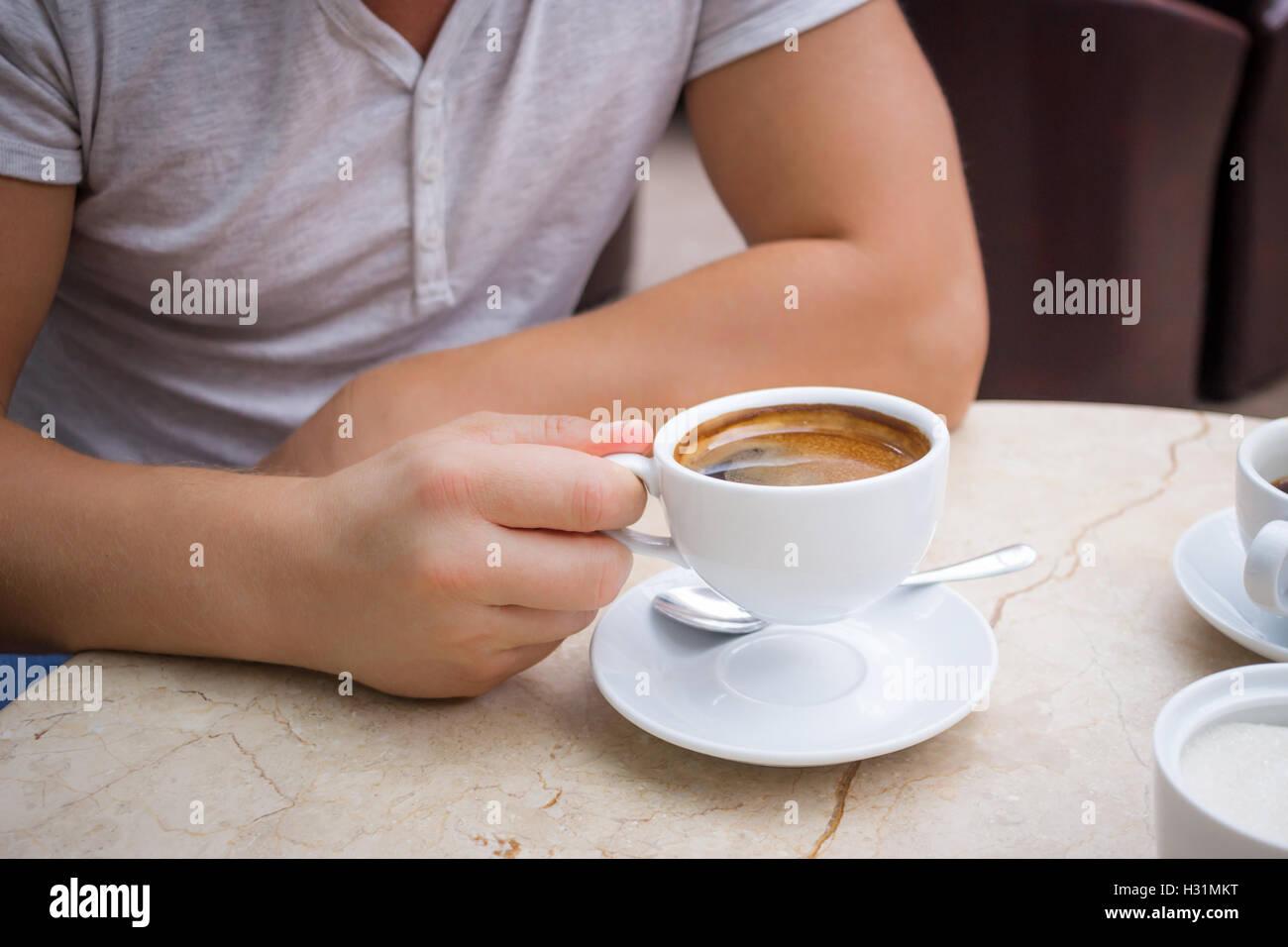 Uomo al tavolo di marmo contiene una tazza di caffè americano nella sua mano Immagini Stock