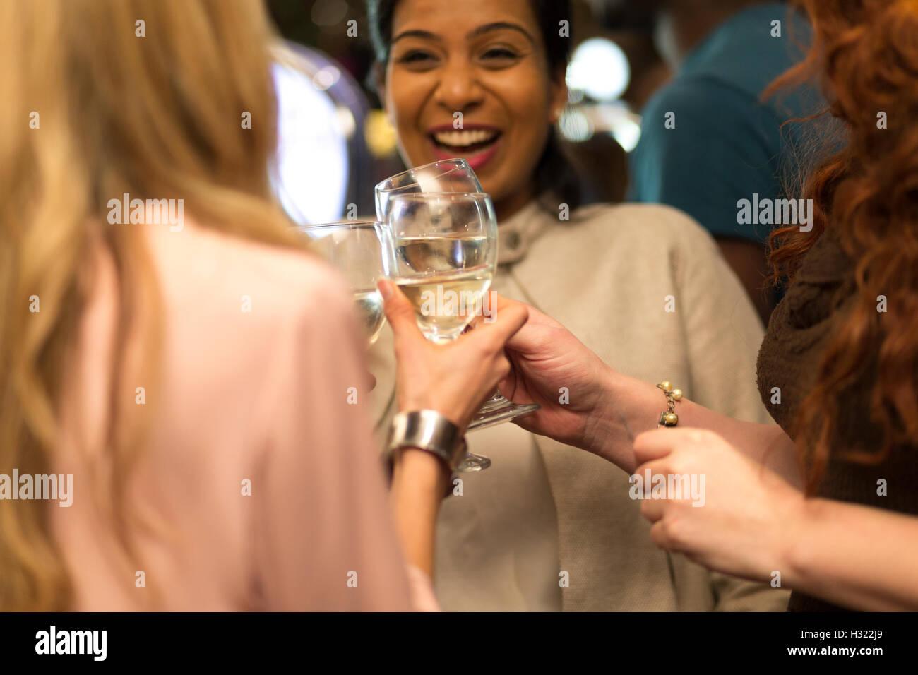 Tre donne tostare i loro bicchieri in un bar Immagini Stock
