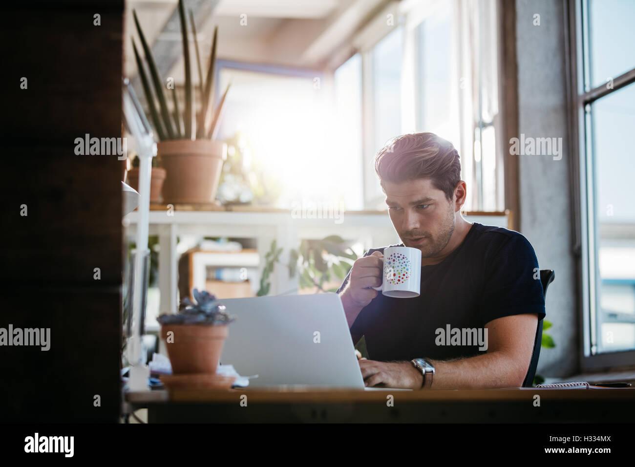 Azienda giovane uomo seduto alla sua scrivania che lavora sul computer portatile e di bere il caffè. Giovane Immagini Stock