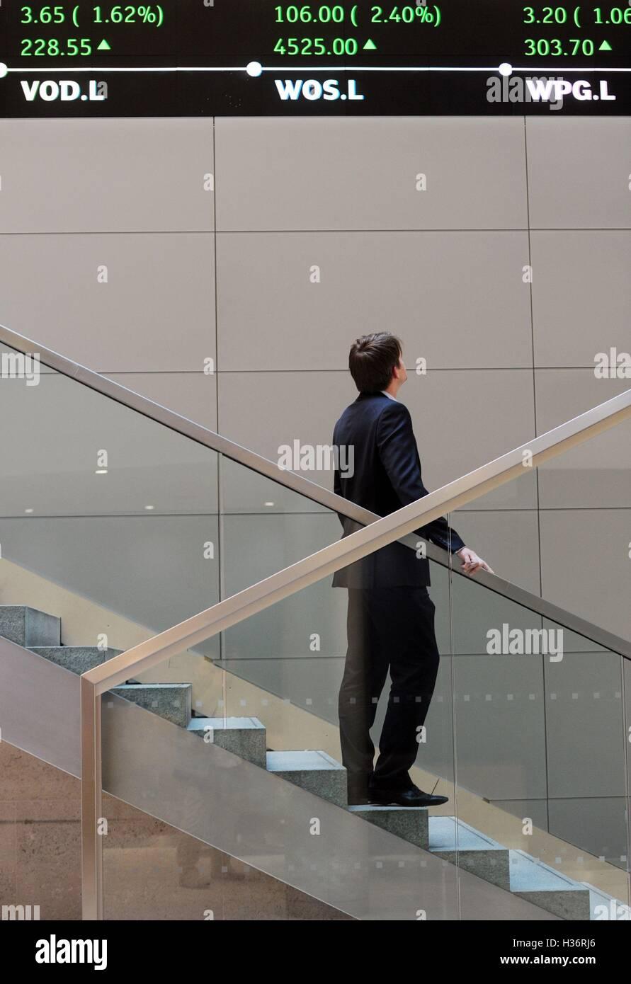 f98ec30a56 Un uomo guarda fino a electronic Ticker tape che mostra il FTSE 100  all'interno