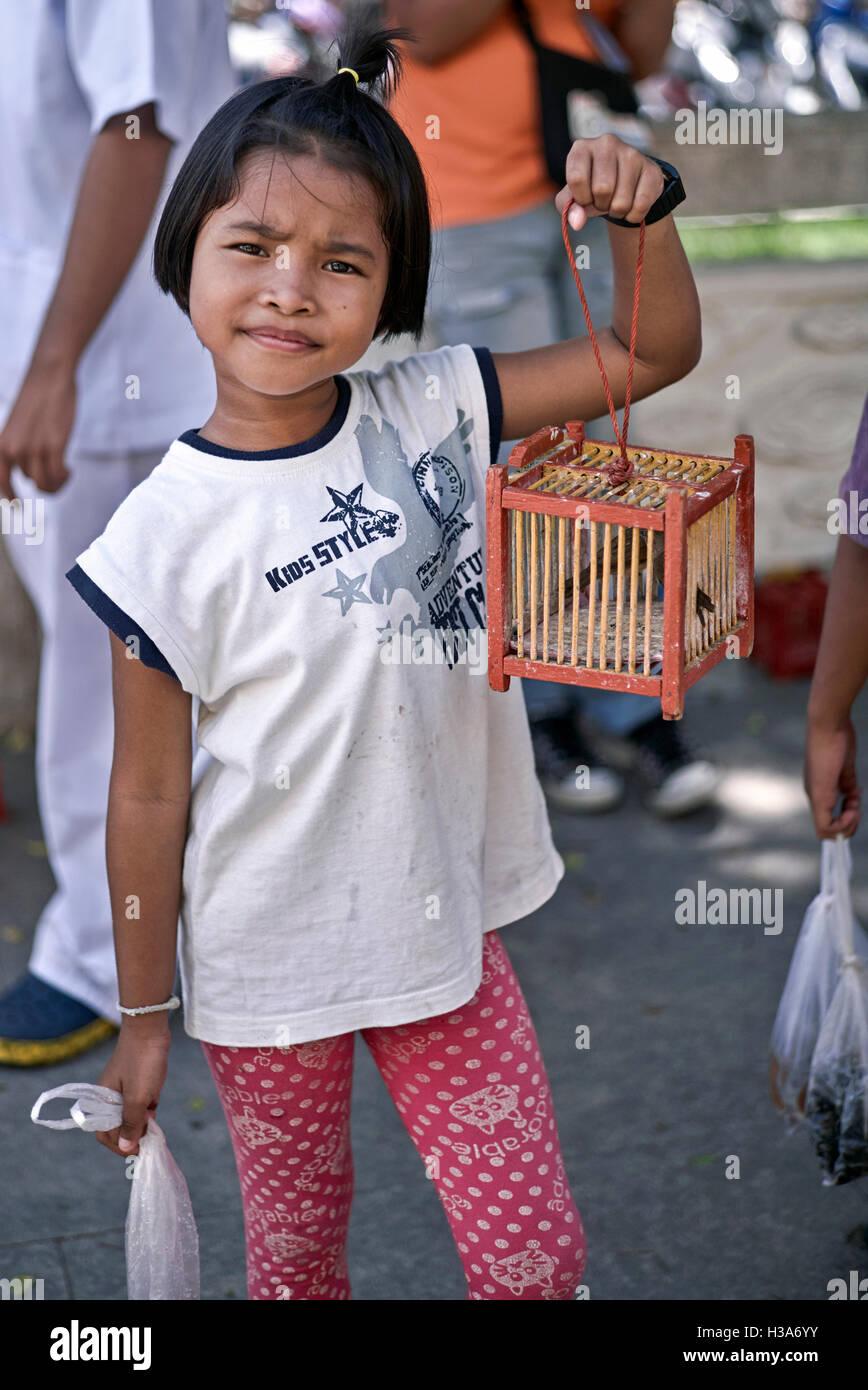 Bambino thailandese con un uccello in gabbia che sarà rilasciato per la fortuna e la fortuna è la convinzione. Immagini Stock