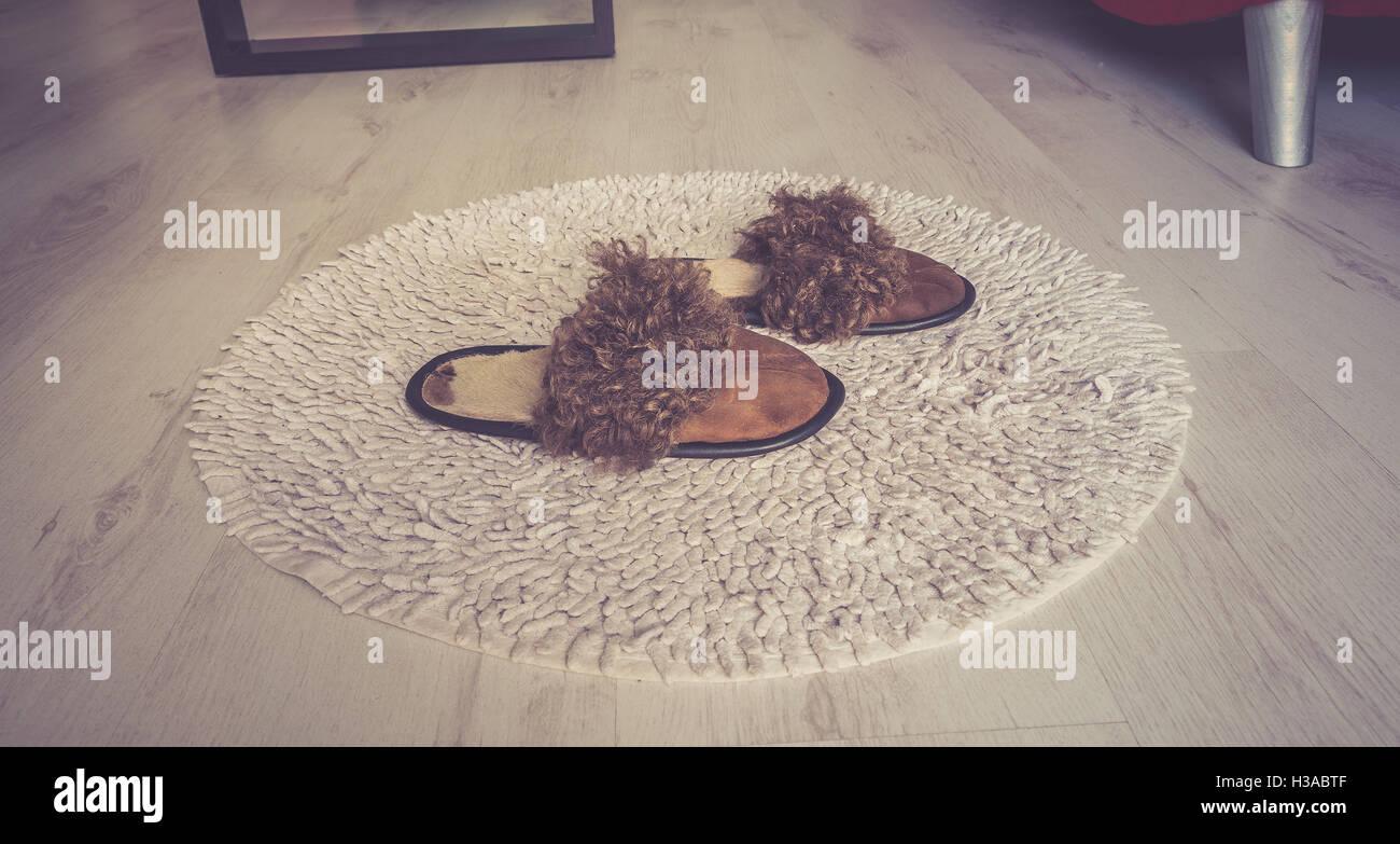 Lana marrone comode pantofole sul tappeto rotondo grigio e