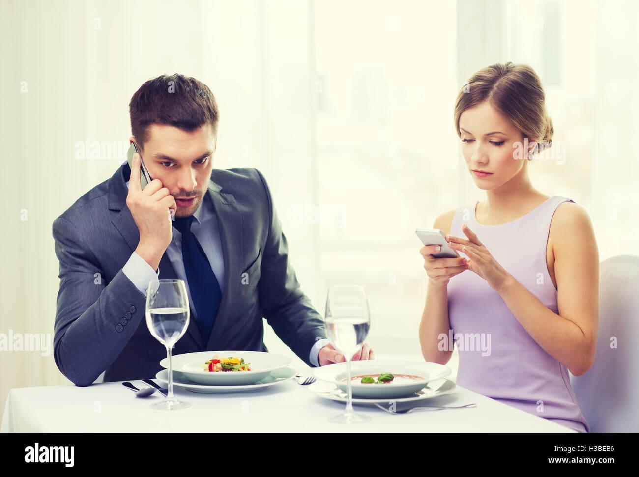 Occupato giovane con gli smartphone al ristorante Immagini Stock