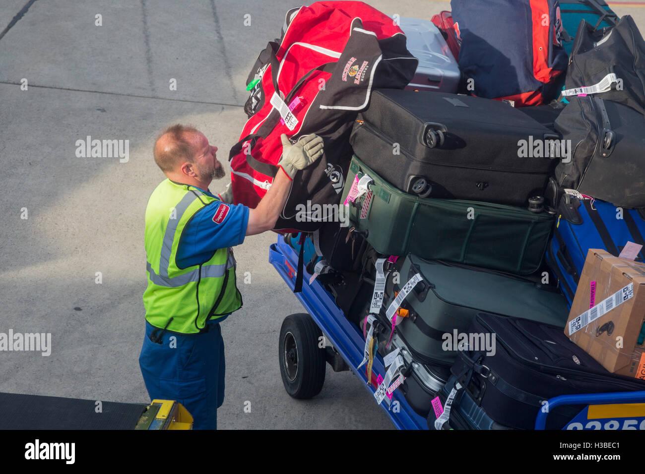 Detroit, Michigan - un lavoratore bagaglio i carichi su di un getto a Detroit Metro Airport. Immagini Stock