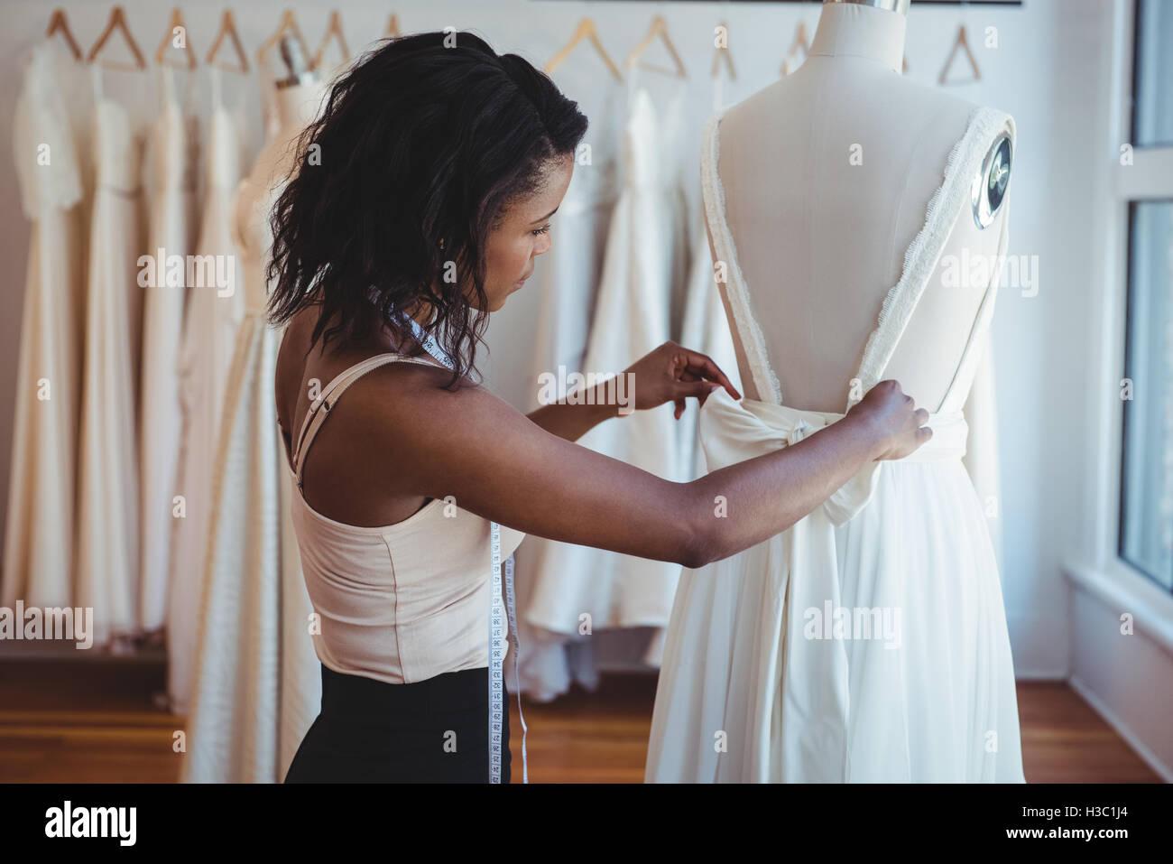 Moda femminile designer regolando il vestito sul manichino Immagini Stock