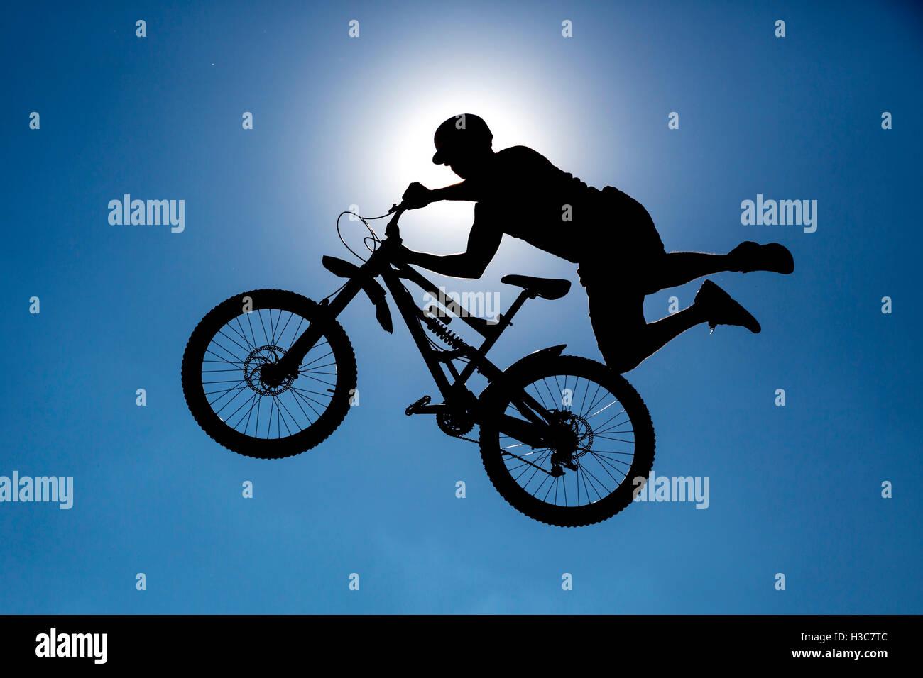 Un extreme rider è rendere uno stile libero saltare da una rampa. Il giovane ragazzo con la bicicletta è Immagini Stock