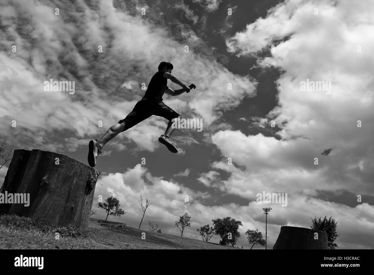 Un colombiano parkour atleta esegue un salto in alto durante una corsa libera la sessione di formazione in un parco Immagini Stock