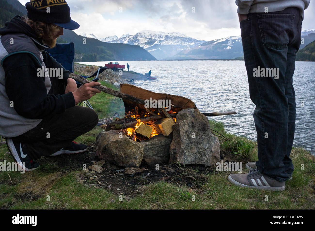 Amici costruisca un fuoco sulla riva di un lago interno della Columbia Britannica Immagini Stock