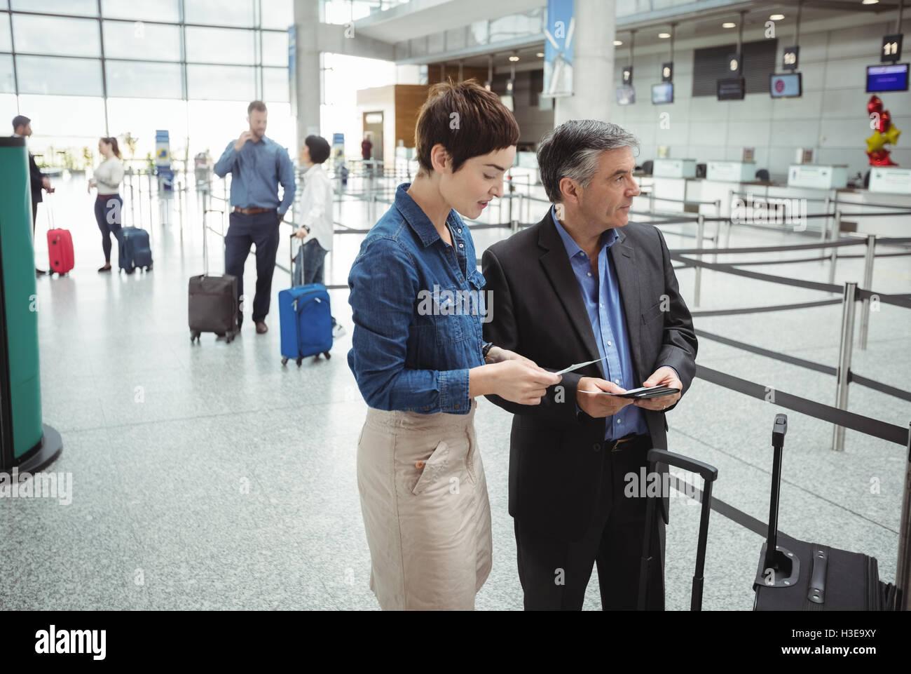 Uomo di affari e donna controllando il loro passaporto Immagini Stock