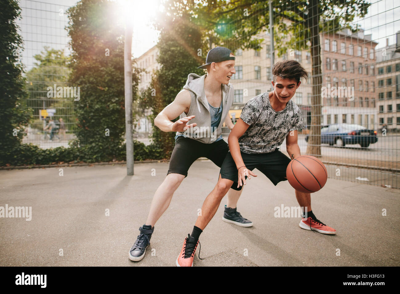 I ragazzi giocare a basket sul tribunale aperto e divertirsi. Giovane uomo dribbling basket con un amico il blocco. Immagini Stock