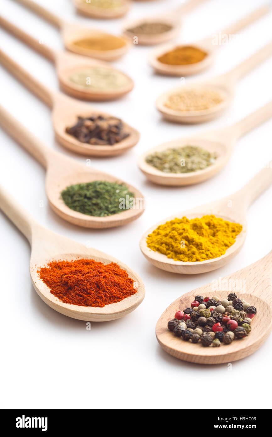 Varie spezie in cucchiai di legno isolato su sfondo bianco. Immagini Stock