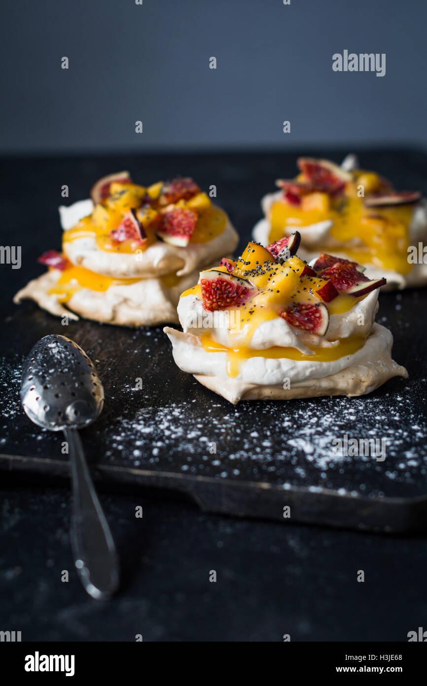 Pavlova dessert con limone cagliata, fichi freschi e semi di papavero. Verticale, il fuoco selettivo Immagini Stock