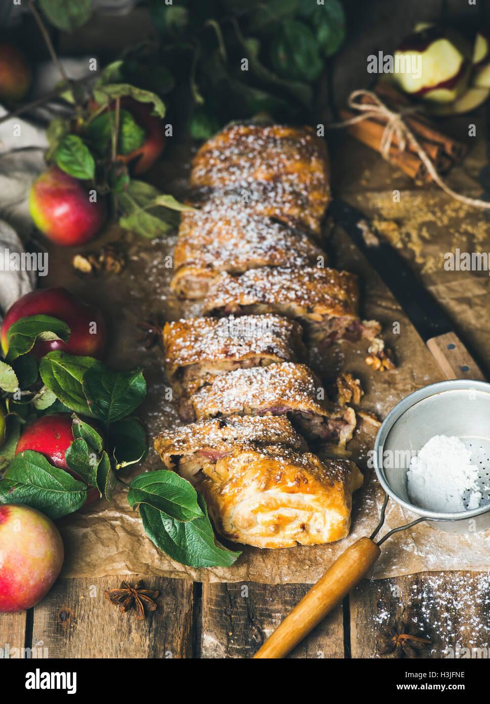 Strudel di mele torta con la cannella, lo zucchero in polvere e mele fresche sulla tavola in legno rustico sfondo, Immagini Stock