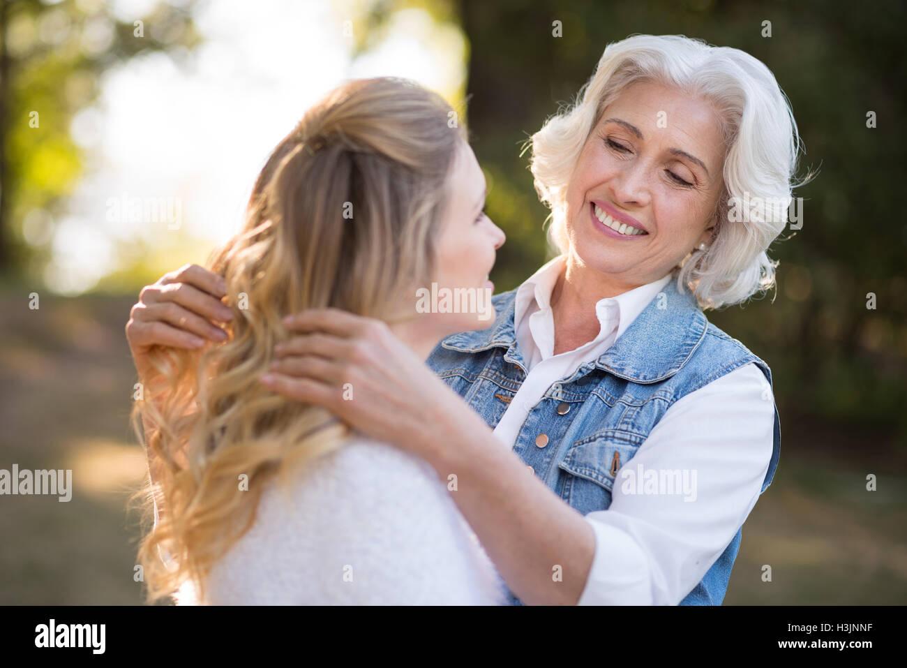 Bella vecchia signora giocando con i capelli di sua figlia Immagini Stock