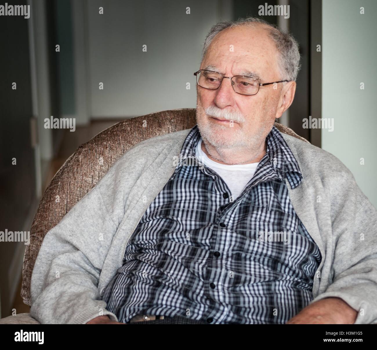 Ritratto di un nonno che indossa un maglione grigio a sedersi su una  poltrona a casa 42fe2d198871