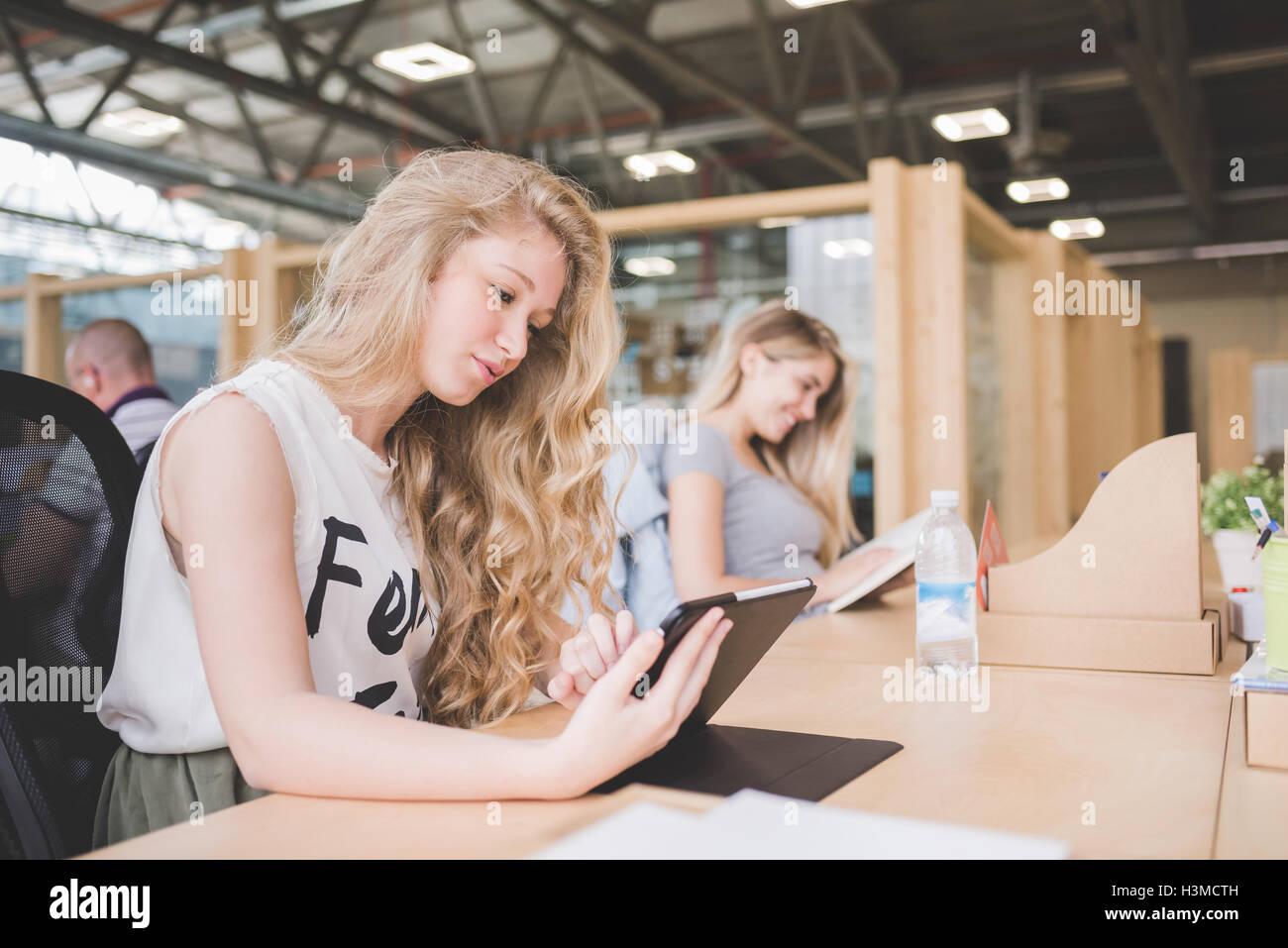 Co-lavoratori che operano su tavoletta digitale in open ufficio del piano Foto Stock