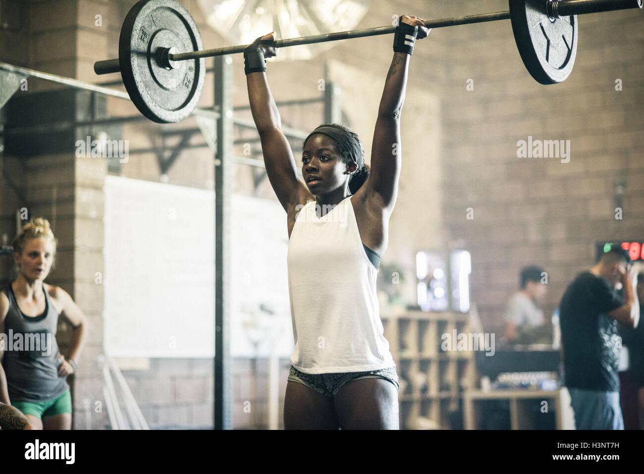 Formazione trasversale di sollevamento atleta barbell in palestra Immagini Stock