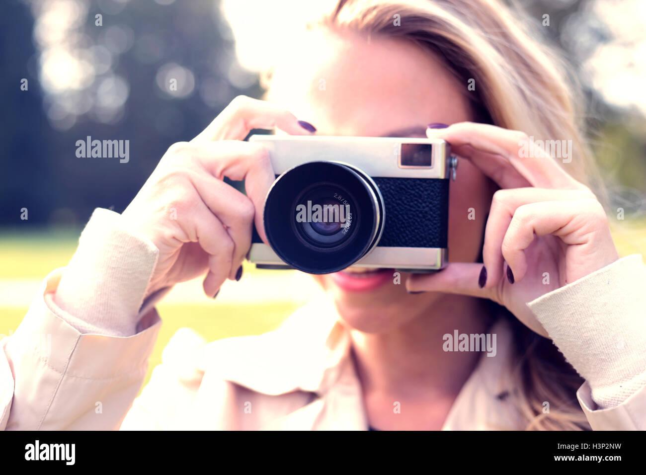 Giovane donna prendendo foto con vecchie foto fotocamera Immagini Stock