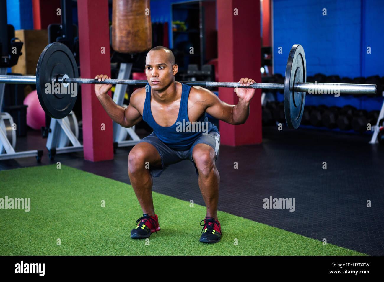 Giovane uomo il sollevamento pesi in palestra per il fitness Immagini Stock