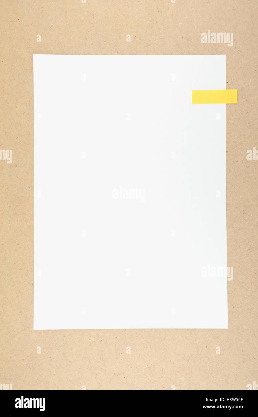 Carta bianca con una nota adesiva sul pannello di particelle. Immagini Stock