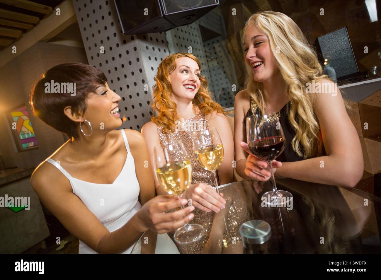 Tre sorridente amico avente un bicchiere di champagne Immagini Stock