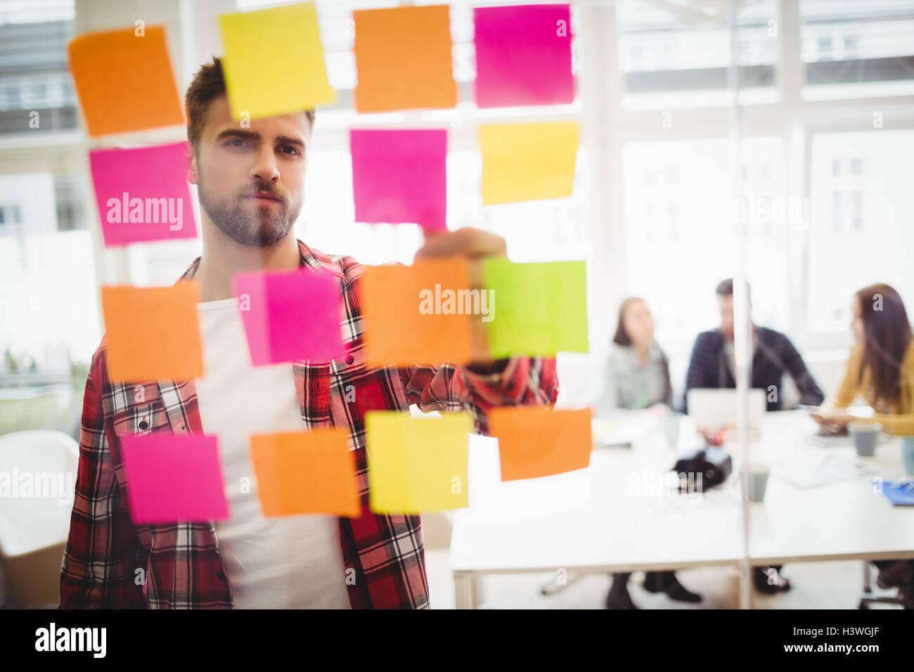 Editor foto guardando colorato sticky notes su vetro Immagini Stock