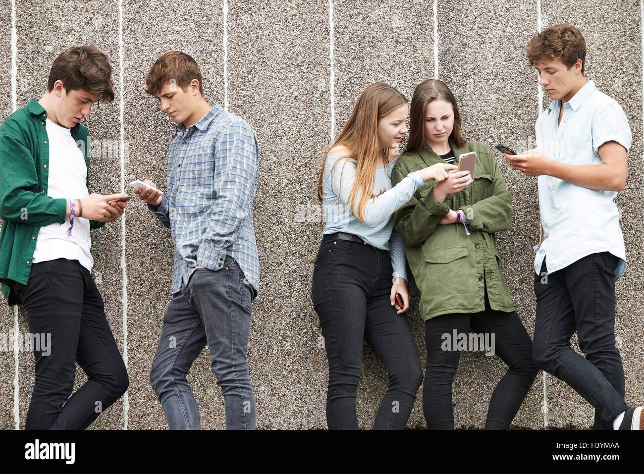 Un gruppo di adolescenti di condivisione del messaggio di testo su telefoni cellulari Immagini Stock