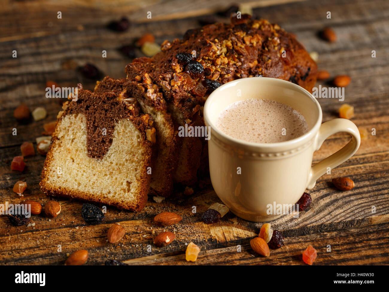 La colazione del mattino con cappuccino e laghetto torta con frutta secca Immagini Stock
