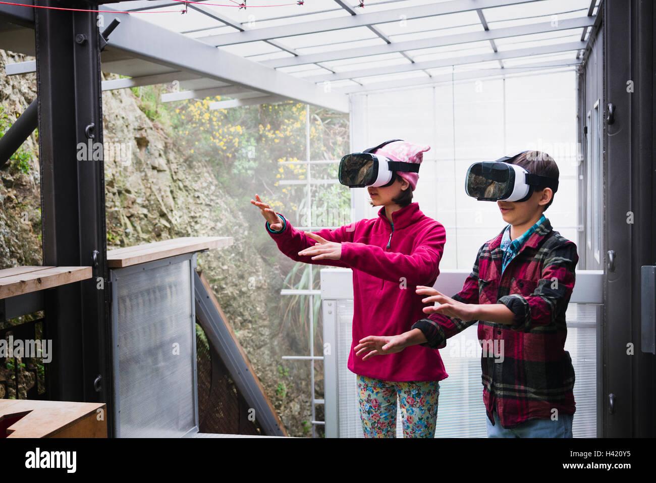 Razza mista del fratello e sorella utilizzando la realtà virtuale occhiali sulla veranda Foto Stock