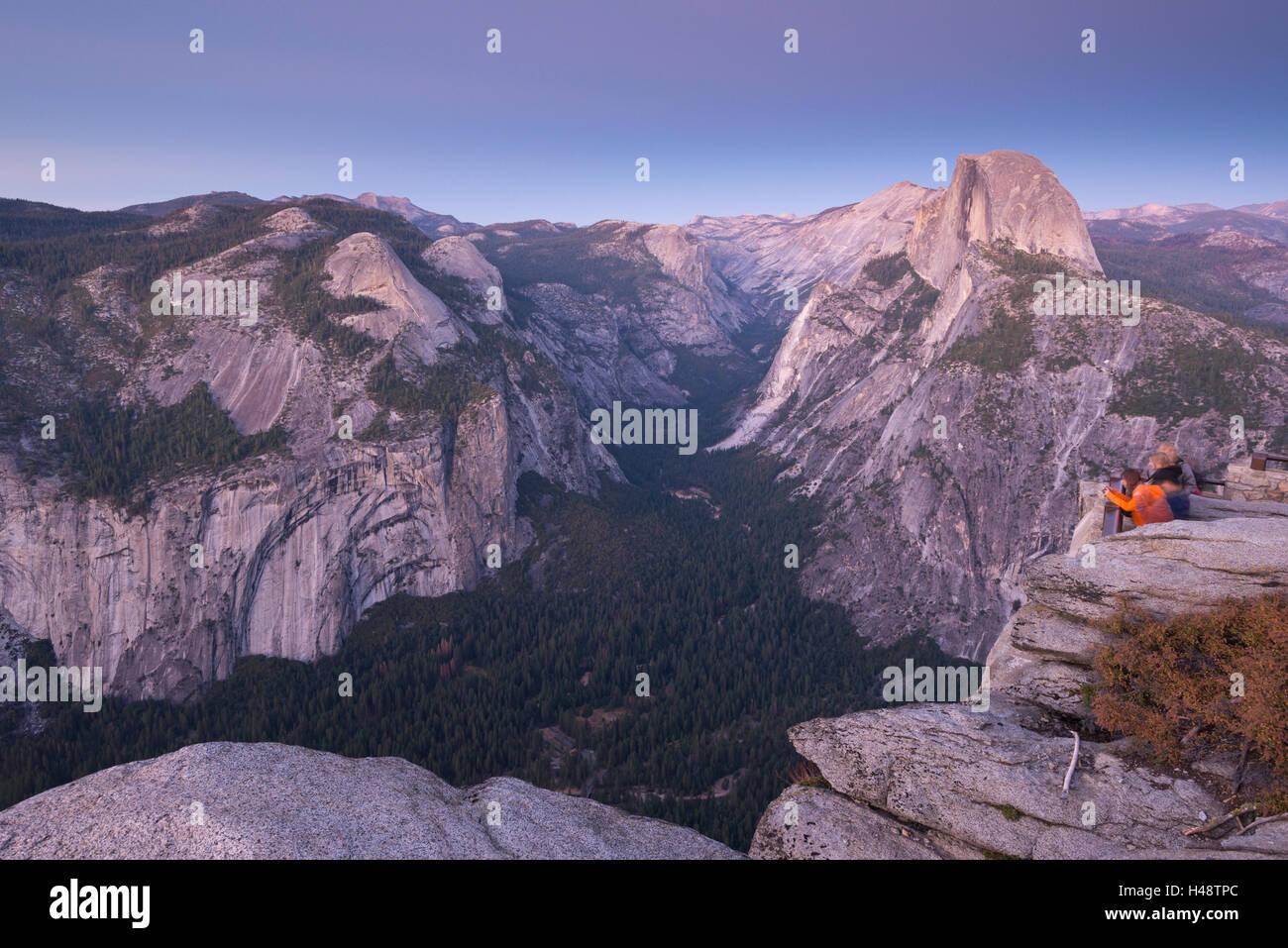 I turisti la visualizzazione di mezza cupola e il Parco Nazionale di Yosemite Valley dal punto ghiacciaio, Yosemite Immagini Stock