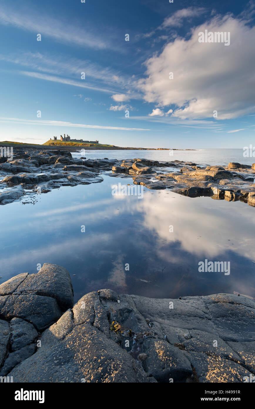 Costa rocciosa con rockpools vicino castello di Dunstanburgh, Craster, Northumberland, Inghilterra. Molla (aprile) Immagini Stock