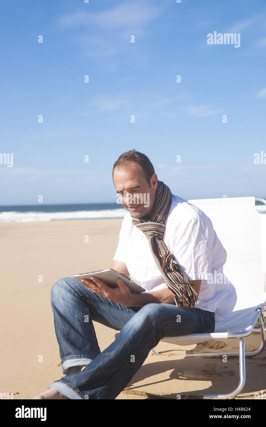 L'uomo utilizza il suo Tablet PC sulla spiaggia, Immagini Stock