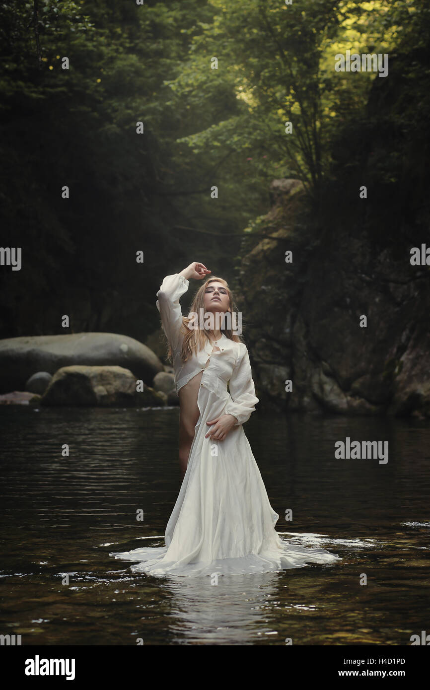 Bella donna in posa sognante ruscello di montagna. Fantasia e surreale Immagini Stock
