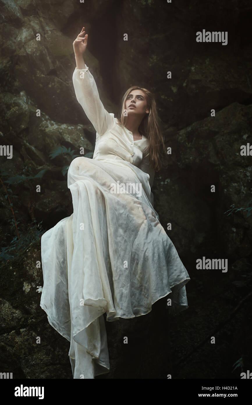 Donna in posa sulle rocce della foresta. Atmosfera sognante Immagini Stock