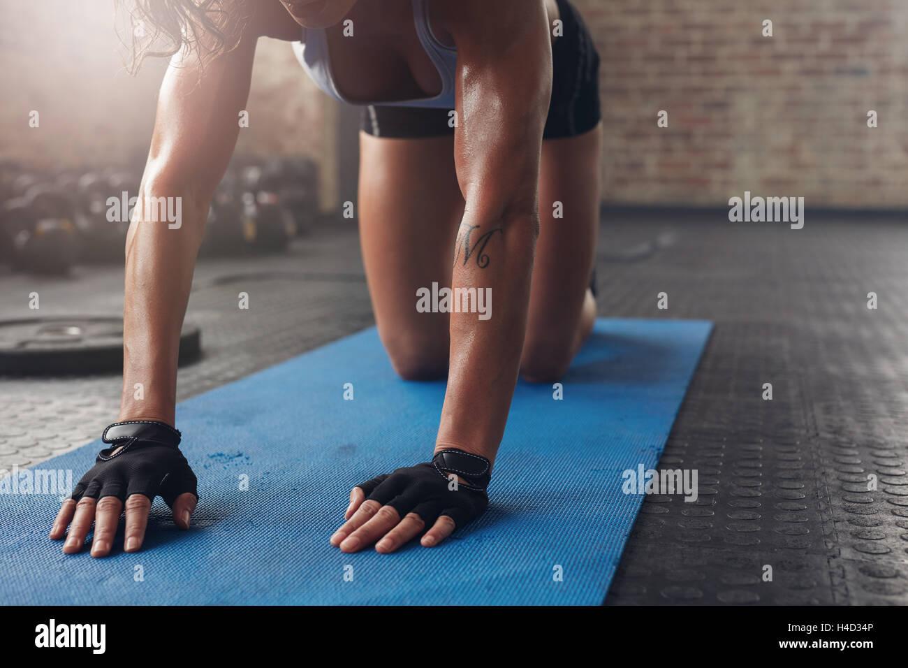 Femmina su esercizio mat facendo stretching allenamento. Focus sulla mano di una donna sul tappetino fitness. Immagini Stock