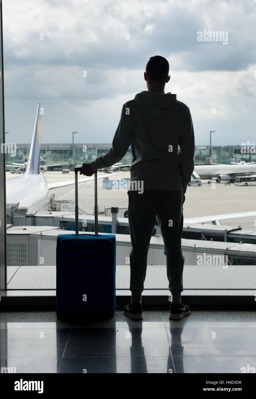 Un adolescente è in attesa su un aeroporto per la partenza Immagini Stock
